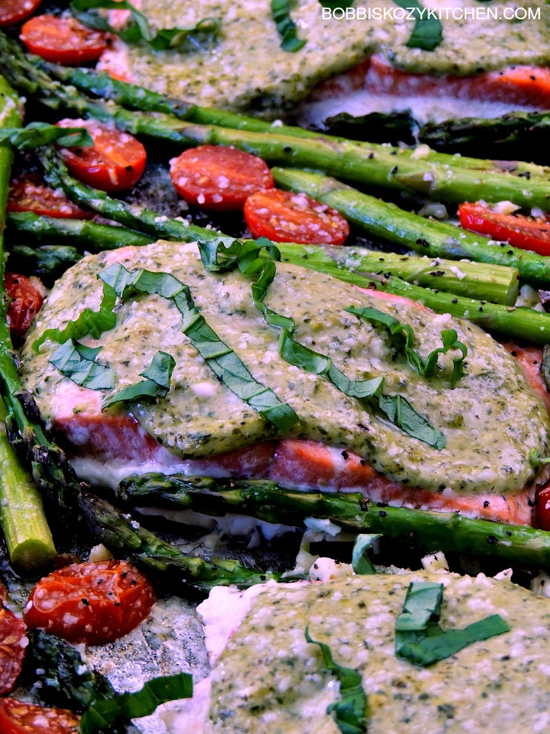 Sheet Pan Pesto Salmon with Asparagus and Tomatoes is quick, and easy, but doesn't scrimp on taste. A perfect weekday supper the whole family will love. From www.bobbiskozykitchen.com
