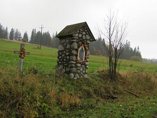 Krzyż i murowana kapliczka przy szosie.