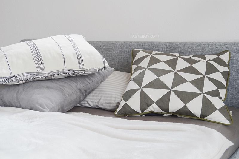 Bett dekorieren schlicht gemütlich im Winter mit Kisen und Wohntextilien in weiß-grau.