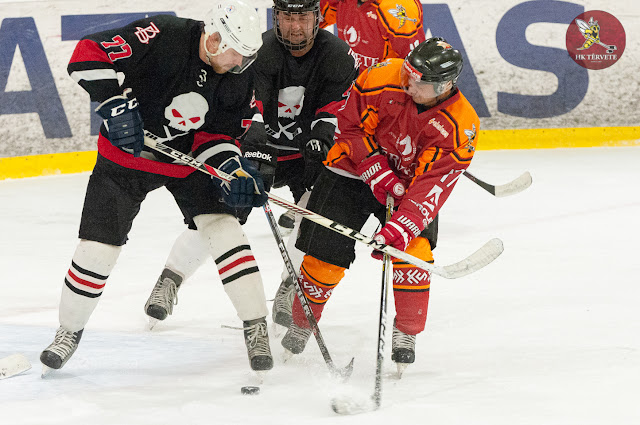 Trīs hokejisti cīnās par ripu ledus laukumā