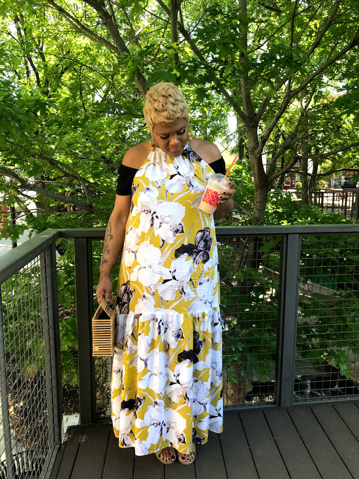 Image: Woman Tangie Bell sharing outfit of the day yellow dress purse, polka dot earrings and a blueberry crisp coffee