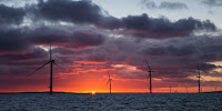 The sun rises behind an offshore wind farm. (Image Credit: Aaron via Flickr) Click to Enlarge.
