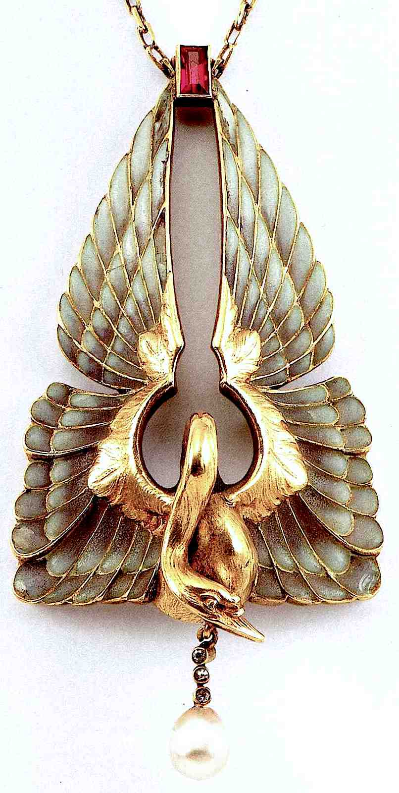 a color photograph of Philippe Wolfers jewelry, a gold bird broach with pearl pendant