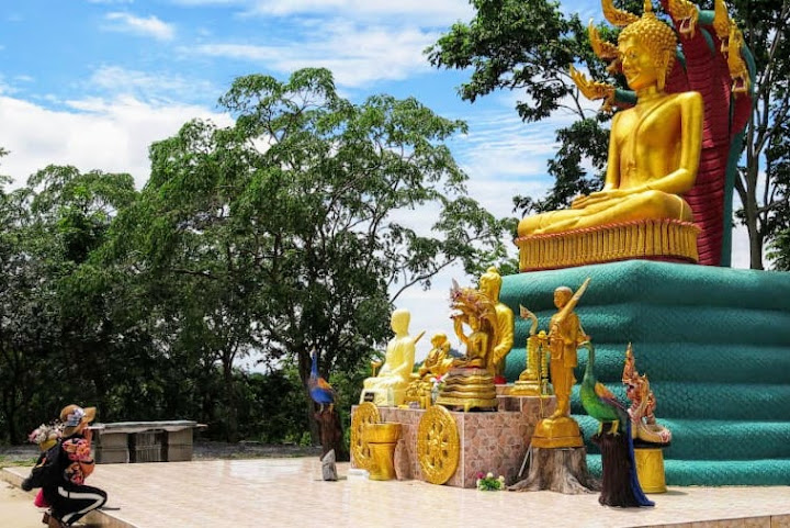"Hilltop Buddha: A Buddhist Thai woman kneels at a larger-than-life statue portraying Buddha protected by a mythical seven-headed ""naga"" snake, which has topped the hill for many years and was not associated with any UFOs before the family's tales."