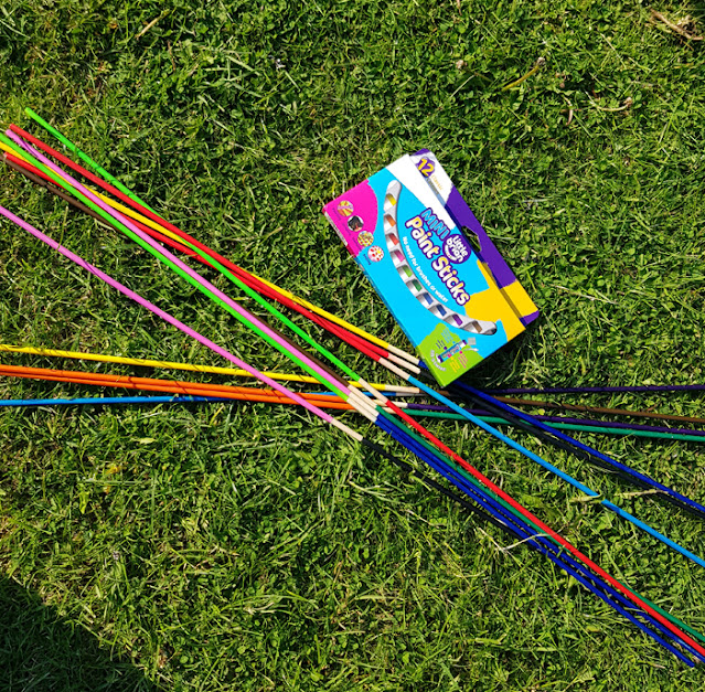 Painting bamboo sticks to use in Giant Garden Kerplunk Game