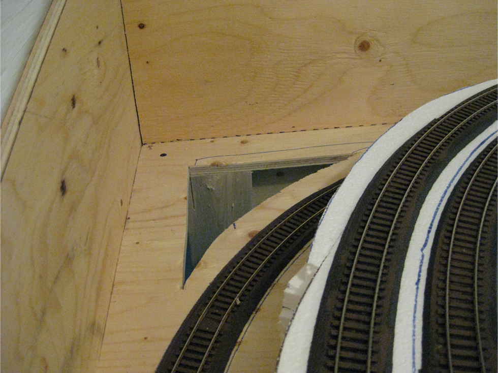 A triangular hole cut through the benchwork next to the model railroad track in the future tunnel