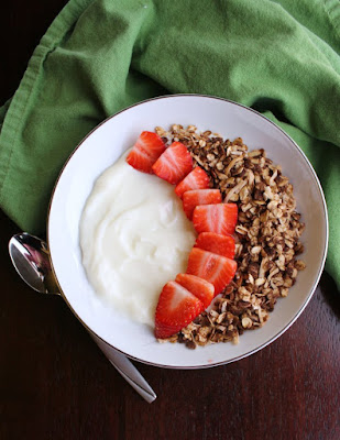 top view of bowl of yogurt with strawberries and chocolate granola