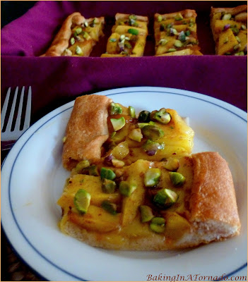 Glazed Mango Tart with Pistachios, a crescent tart topped with ripe mango slices, baked with a glaze, then topped with crunchy topped pistachios. | Recipe developed by www.BakingInATornado.com | #recipe #dessert