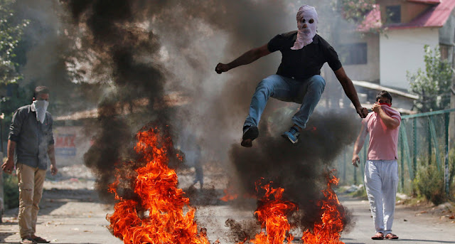Image Attribute: A man in a balaclava jumps over burning debris during a protest against the recent killings in Kashmir, in Srinagar, India September 12, 2016. REUTERS/Danish Ismail/File Photo