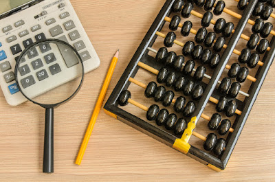 On a desk lie a calculator and an abacus with a pencil and magnifying glassw