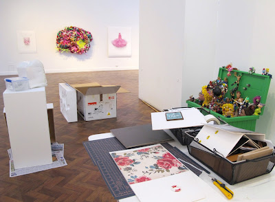 View across a gallery during install, showing a table with a miniature scene being put together and various artworks in the background, mounted or still in packaging.