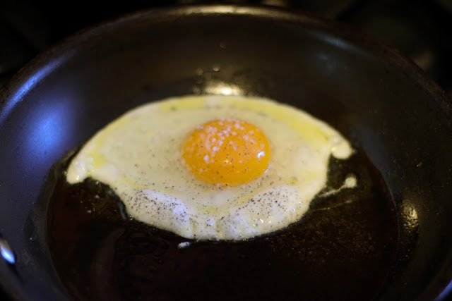 An egg frying on the frying pan.