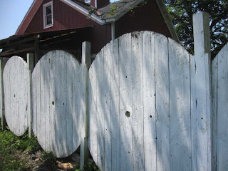 Tops and bottoms of large spools used as fence panels with posts between