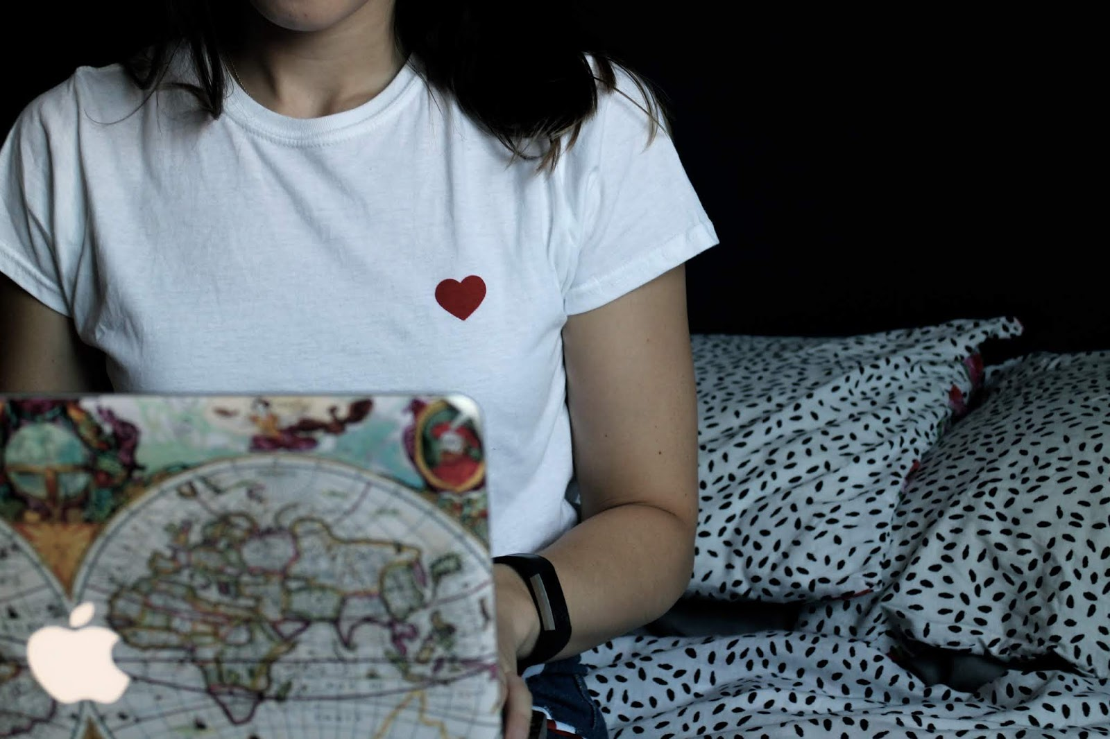 Close up of heart on a white t-shirt, girl holding a laptop