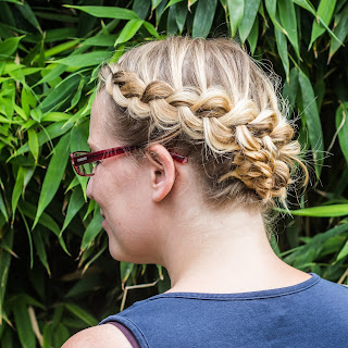 Me looking away from the camera with my hair in a plait which is wrapped around my head. It looks nicer than that sounds