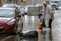 In this Sept. 30, 2015 file photo, a hotel guest carries his shoes as he is escorted to his car along in Miami Beach, Fla. The street flooding was in part caused by high tides due to the lunar cycle, according to the National Weather Service. A new scientific report finds man-made climate change played some kind of role in two dozen extreme weather events around the world in 2015. But it also detected no global warming fingerprints in a handful of other weird weather instances. (Credit: AP Photo/Lynne Sladky, File) Click to Enlarge.