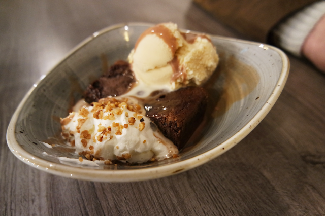 A chocolate brownie with peanut butter icecream, whipped cream, and chopped nuts