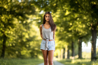 Linda chica paseando por un parque mirando a cámara