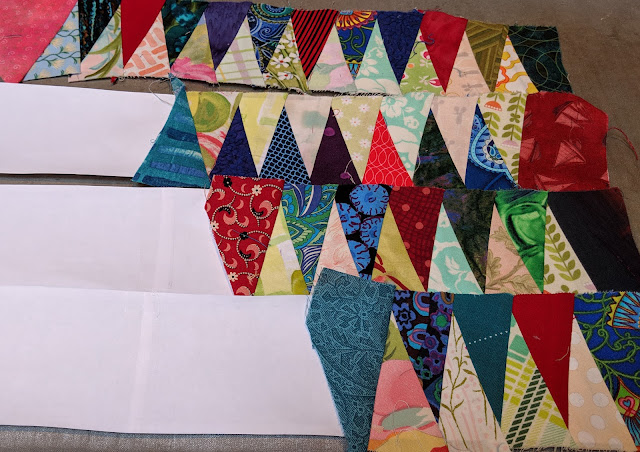 Colorful paper-pieced isosceles triangles are sewn to alternate sides of the sashing strip so there is a light and a dark side.