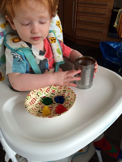 Toddler finger painting the can