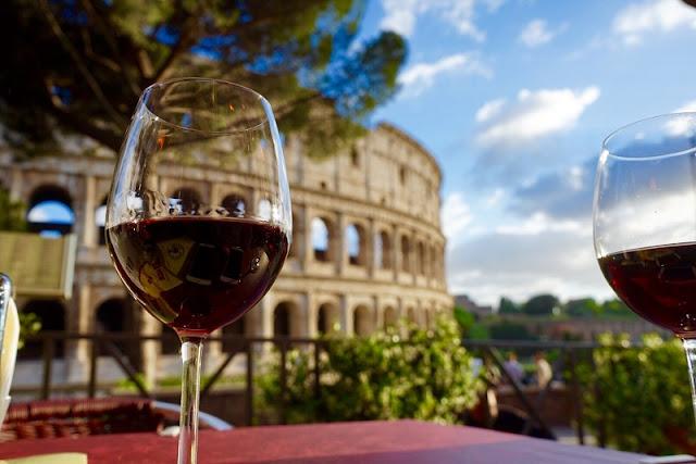 Copo de vinho e Coliseu de Roma de fundo