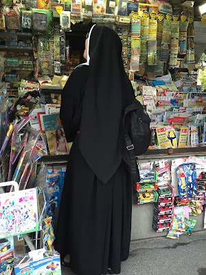 A polish nun at a newsstand in Bergamo