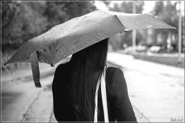 người phụ nữ đi dưới mưa buồn