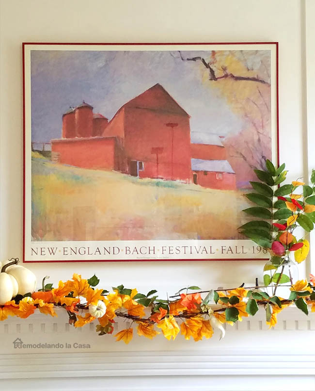 red barn, print, yellow leaves garland, white pumpkin, vase full of leaves