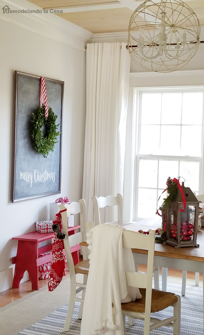 Chalkboard holding a boxwood wreath a top a red bench with dining table in front.