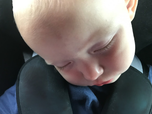 A close up of a toddler asleep in a car seat with her head at an angle