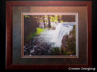 Cramer Imaging's photograph of a lit up award-winning photo depicting a waterfall in a simple double mat and wooden frame