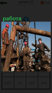 рабочие осуществляют работу с трубами на буровой