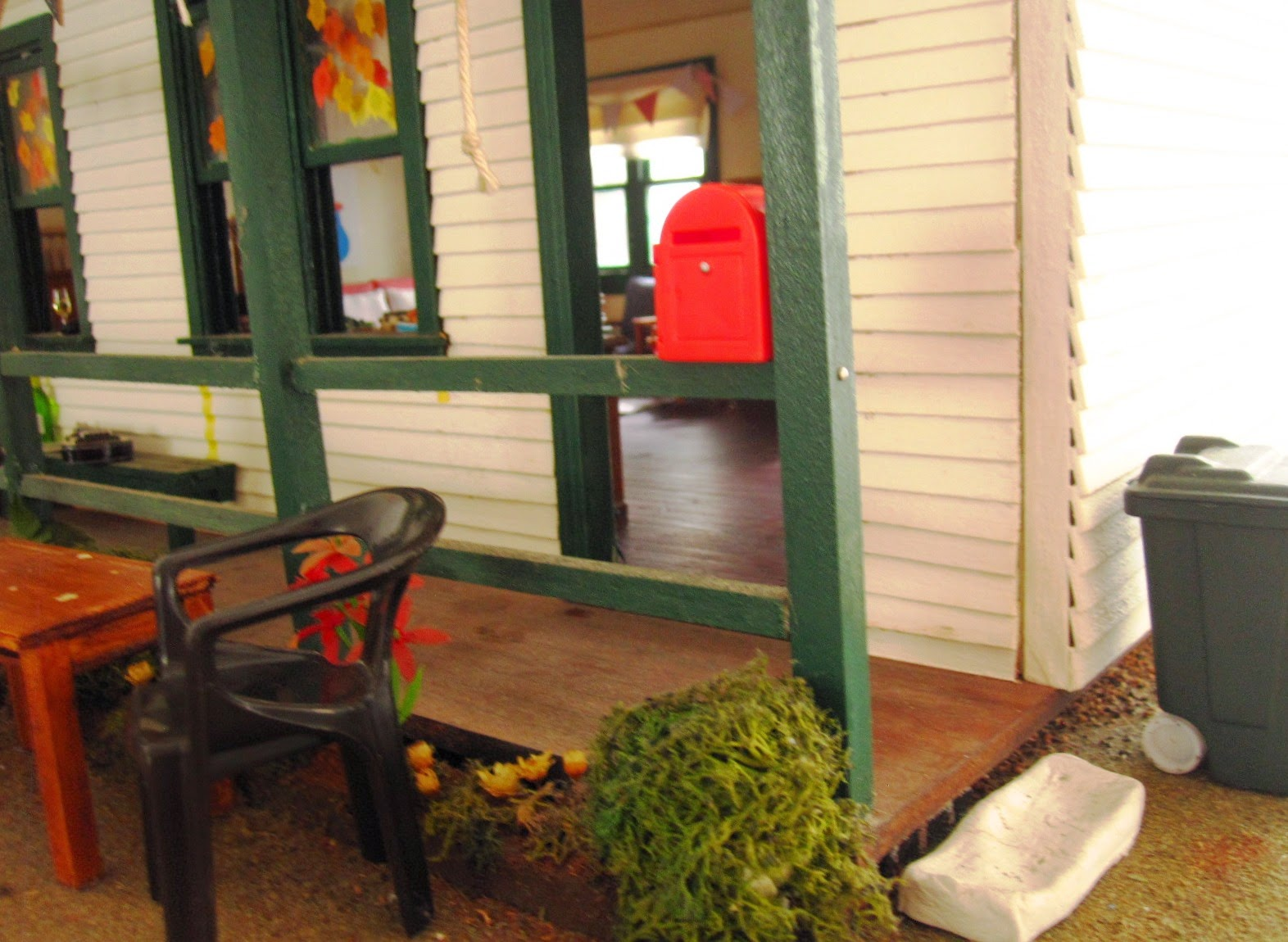 Entry to a miniature dolls' house school with garden chair and a table outside.