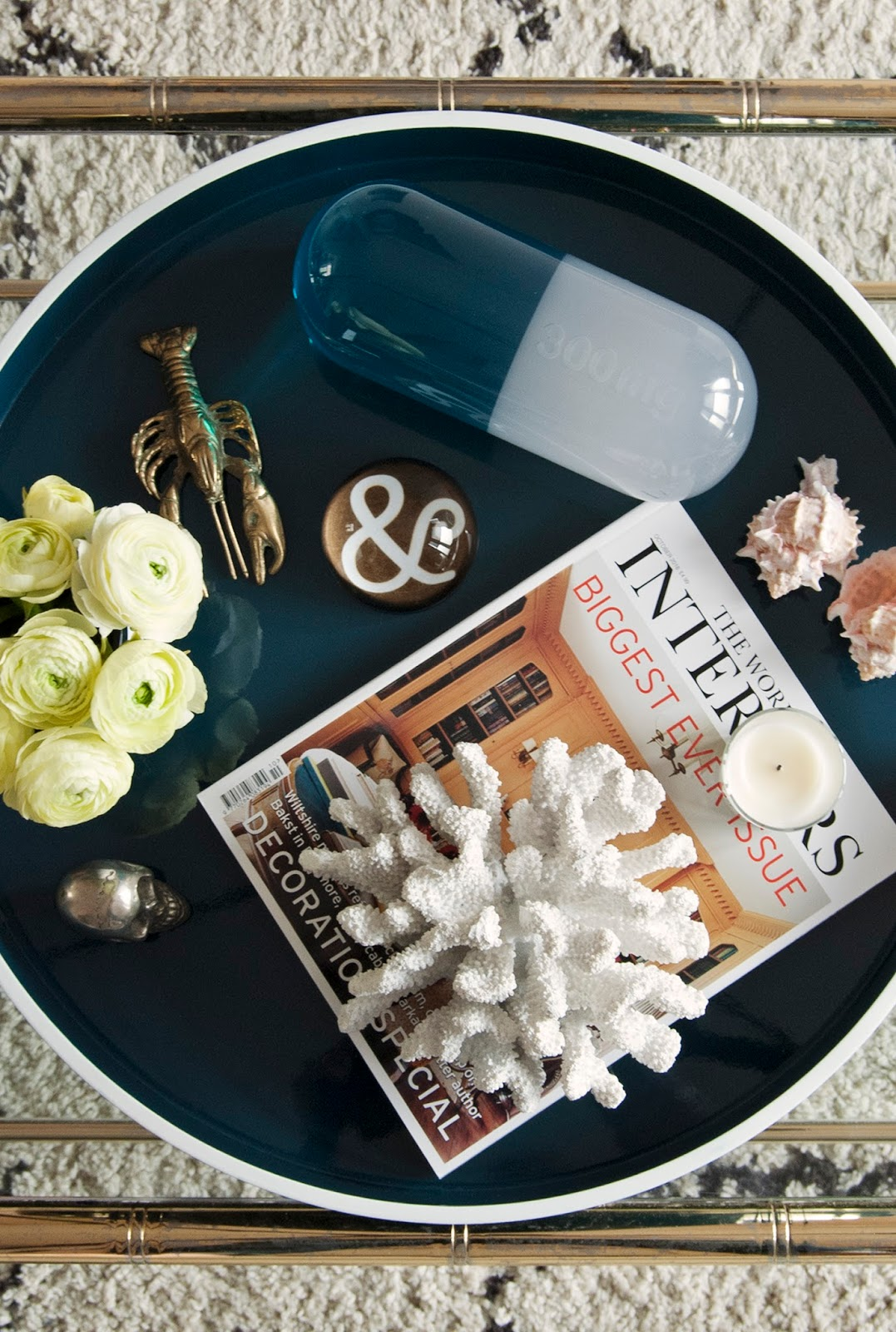 Amara Shoppable Home Inspiration Pages - French For Pineapple Blog - flatlay tray with cool objects jonathan adler lucite pill, vintage lobster, ampersand paperweight, pink shells and white coral