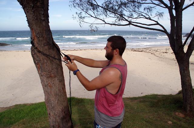West Coast Hammocks male putting up tree friendly straps