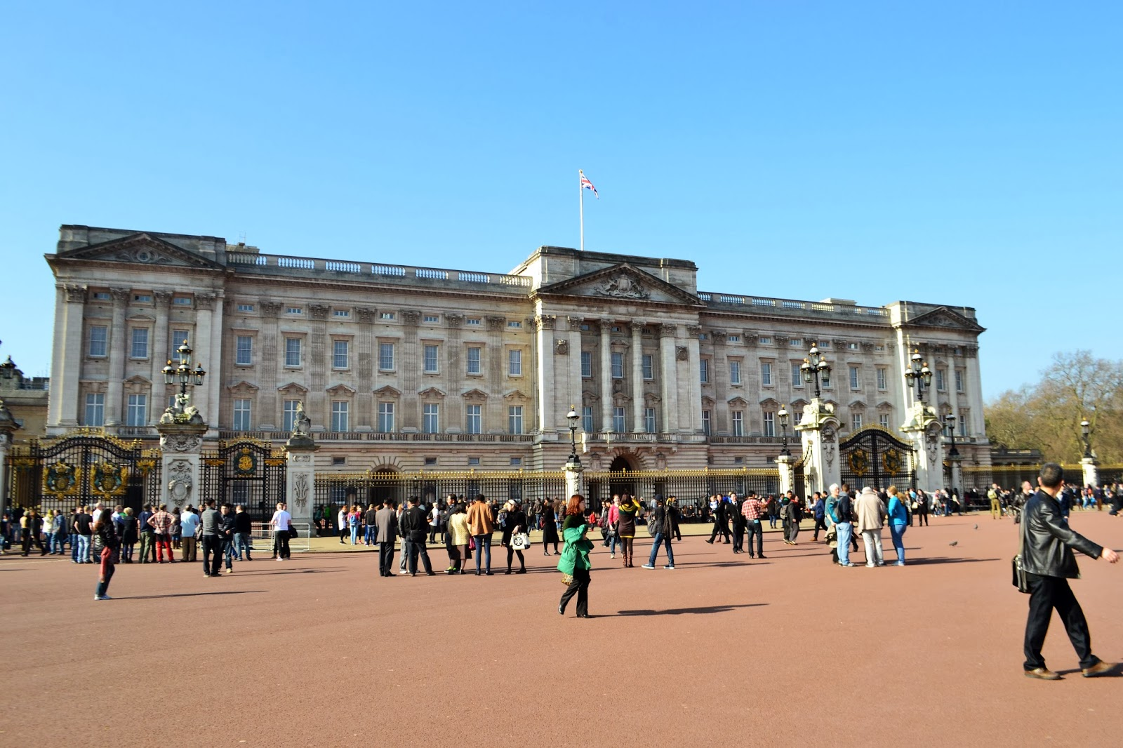 Another view of buckingham palace. the road outside is busy with tourists