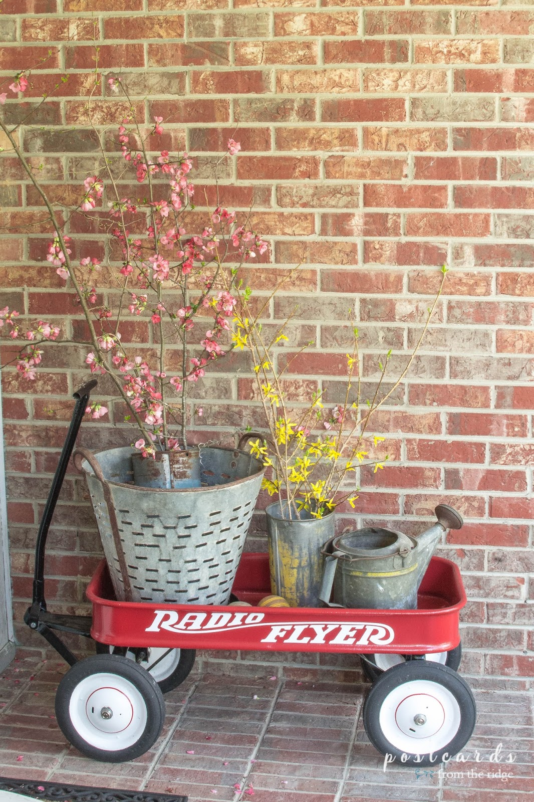 red wagon with flowering branches and vintage sap buckets