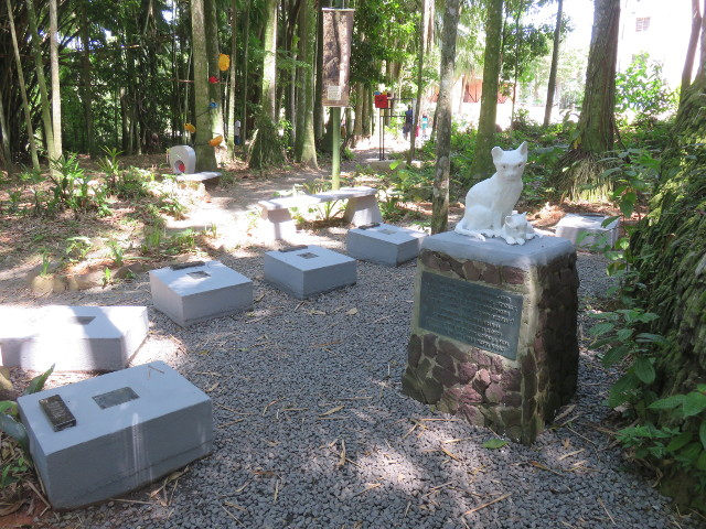 a cats grave yard with some cats tombs and a cat statue