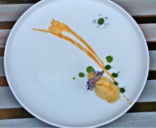Un plato de diseño con varias cremas y una croqueta