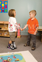 girl and boy shake hands NAMC montessori children grace courtesy practical life activity