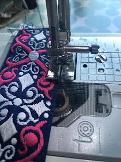 Using a sewing machine to sew the trim to the strap