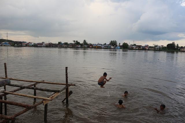 Anak-anak meloncat dengan bahagia ke sungai Kapuas