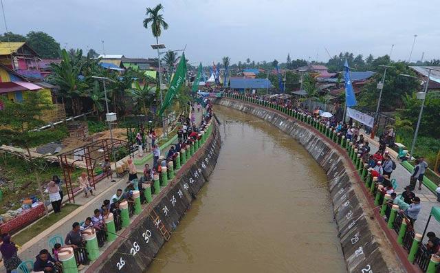 Banyak cara untuk menggaet wisatawan.  Salah satunya lewat lomba.  Seperti yang dilakukan ratusan warga Sumberadi, Guntung Paikat Banjarbaru ini.  Untuk mempromosikan objek wisata Kampung Pelangi, mereka menggelar lomba memancing di sepanjang Sungai Kemuning, Minggu 17 September 2017.
