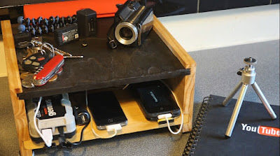 Stone topped wooden platform with various electronics charging