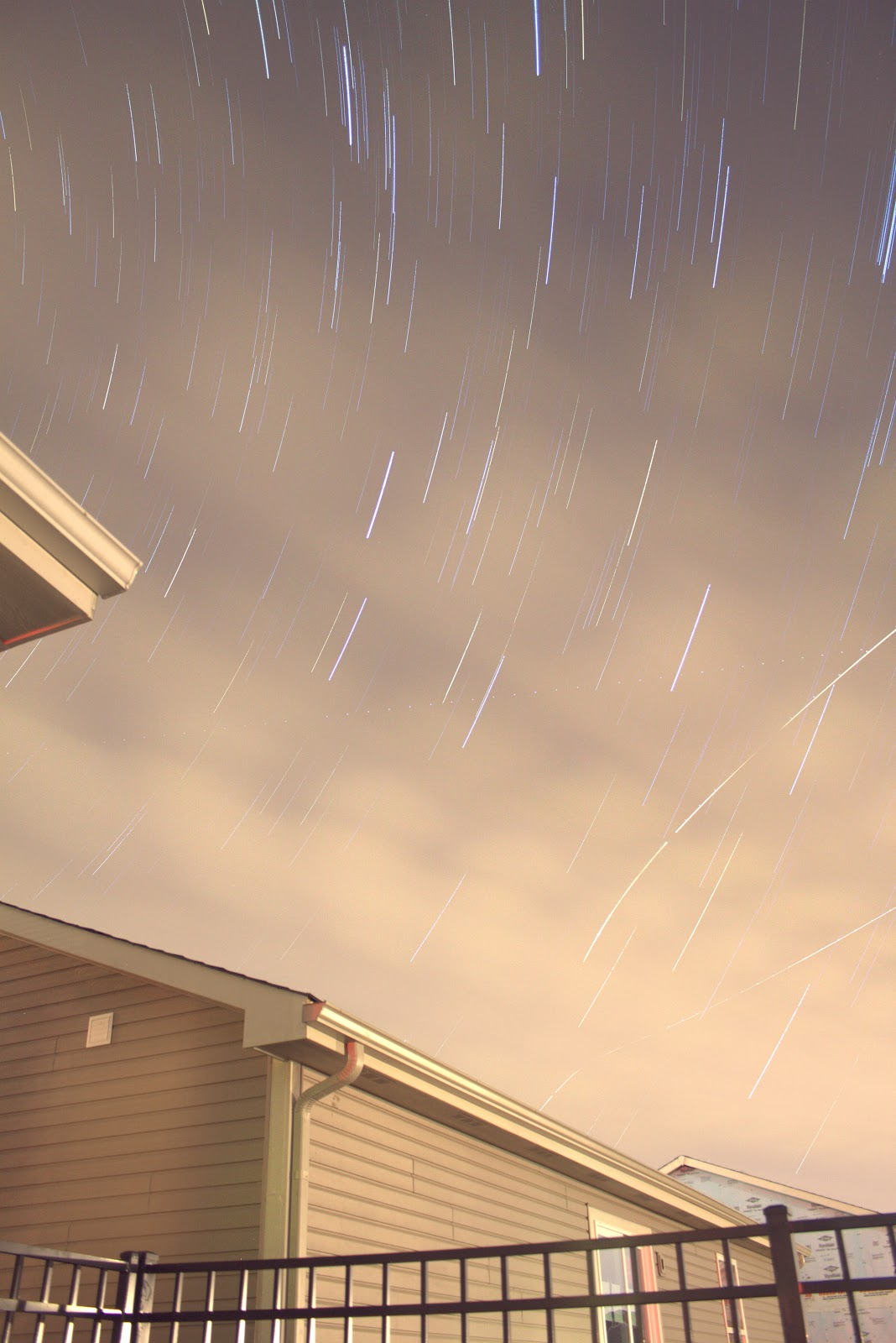 cloudy star trails over house