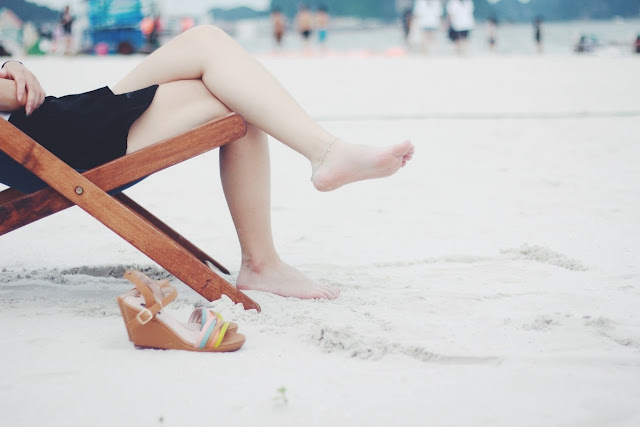 A pair of legs on a deckchair on a beach with a pair of sandals at the side.