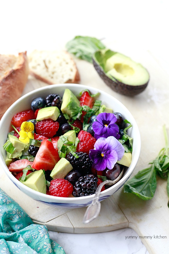 Beautiful salad with strawberries, blackberries, raspberries, avocado, basil, and white balsamic.