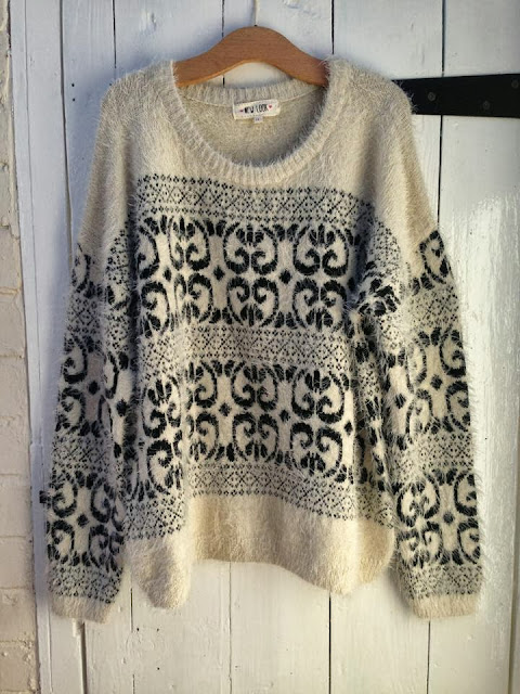 Full image of the fluffy New Look jumper with a black heart shaped pattern repeated across the jumper