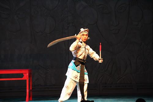 Ator da Ópera de Pequim no palco com uma vela e uma espada