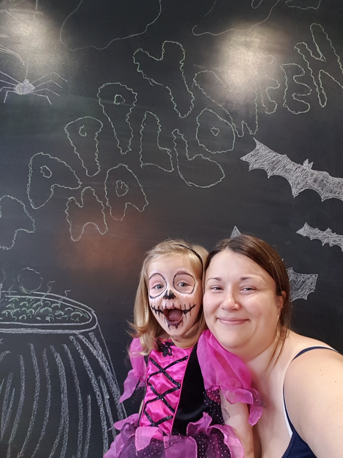 young girl in a halloween costume in front of blackboard art wall